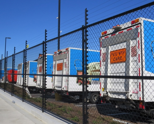 Image showing a row of waste management trucks behind a Fencerite chainlink security fence