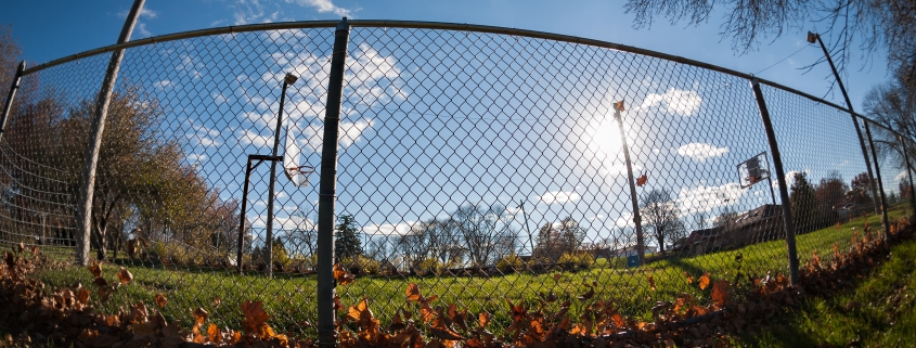 Image showing a sports field with blue sky up above, looking through chainlink fencing