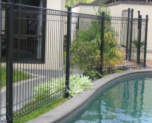 Image showing a curving residential swimming pool surrounded by pool fencing