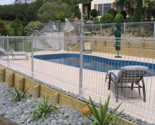 Image showing a kidney shaped residential swimming pool surrounded by pool fencing and landscaped gardens