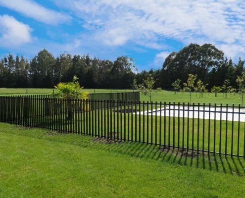 Image showing pool fencing surrounding a pool with beautiful green grass in a park-like setting