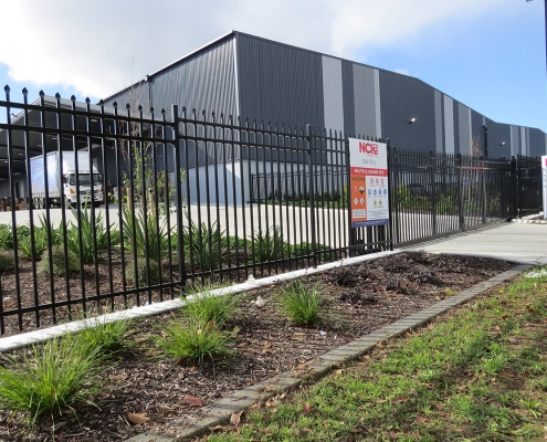 Image showing a black aluminium security sliding gate, in front of the NCI Packaging building in Auckland, installed by Fencerite