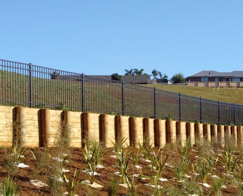 Image showing roadside native plants leading up to a retaining wall with balustrade at the top, in a new subdivision, installed by Fencerite