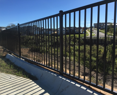 Image showing black balustrades, bordering a gully and residential area in the background, installed by Fencerite
