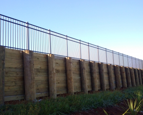 Image showing a retaining wall with black balustrades at the top, installed by Fencerite