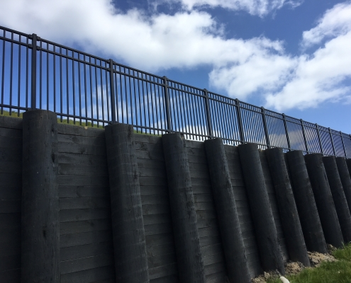 Image showing the view looking up at the top of a retaining wall, with black balustrades, installed by Fencerite