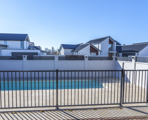 Image showing black aluminium pool fencing and gate, enclosing a modern swimming pool area in residential grounds