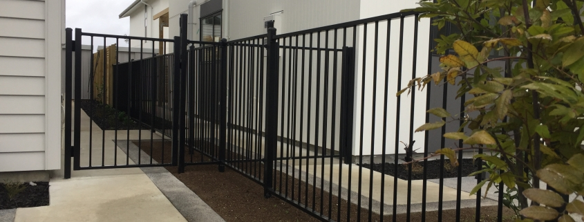 Image showing a black aluminium fence and gate separating two residential buildings, installed by Fencerite