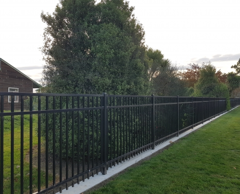 Image showing a black aluminium fence, bordering a residential garden, installed by Fencerite