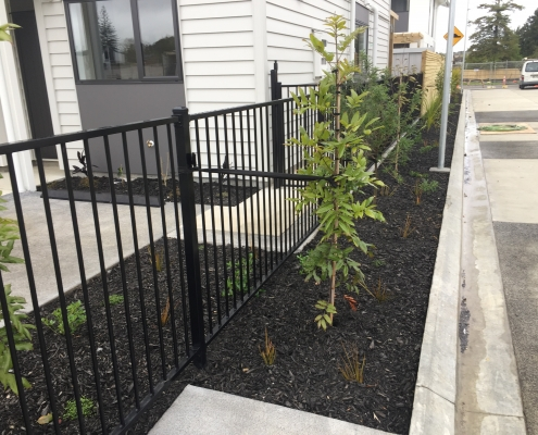 Image showing a black aluminium fence surrounding a residential building with gardens, installed by Fencerite
