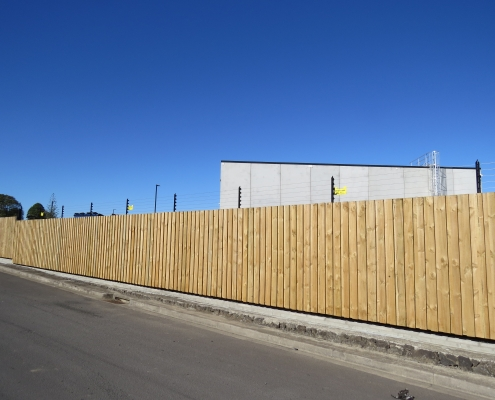 Image showing a wooden security fence surrounding an industrial building, installed by Fencerite