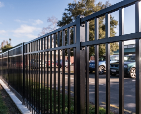 Image showing a close up view of black aluminium school fencing, bordering a school carpark