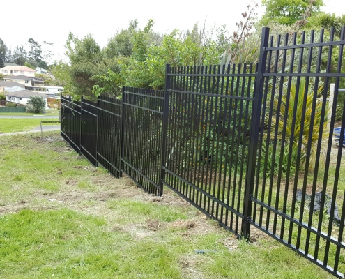 Image showing black aluminium school fencing, bordering school grounds, going down a grassy hill
