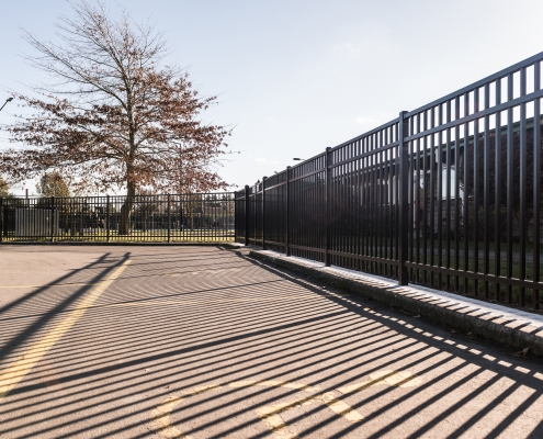 Image showing a school carpark with bordering black aluminium school fencing, installed by Fencerite