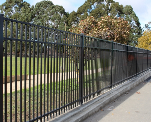 Image showing a black aluminium school fencing, bordering school playing fields, installed by Fencerite