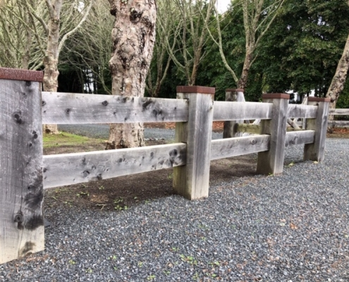Image showing a wooden fence, bordering a rural driveway, installed by Fencerite