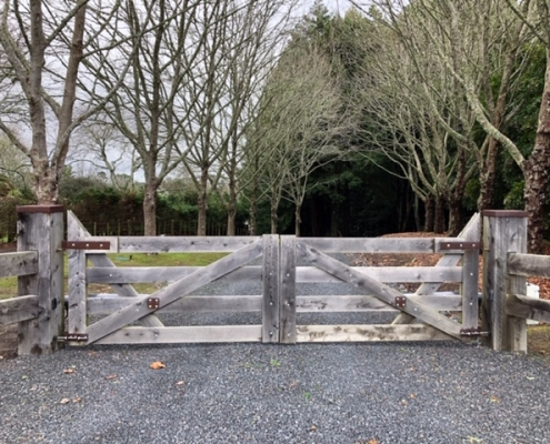 Image showing a wooden gate at the entrance of a rural driveway, installed by Fencerite